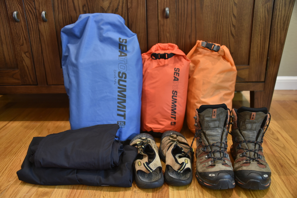 Waterproof bags to hold clothes and sleeping bag.  Plus boots, sandals, and waterproof outer layer pants/jacket.
