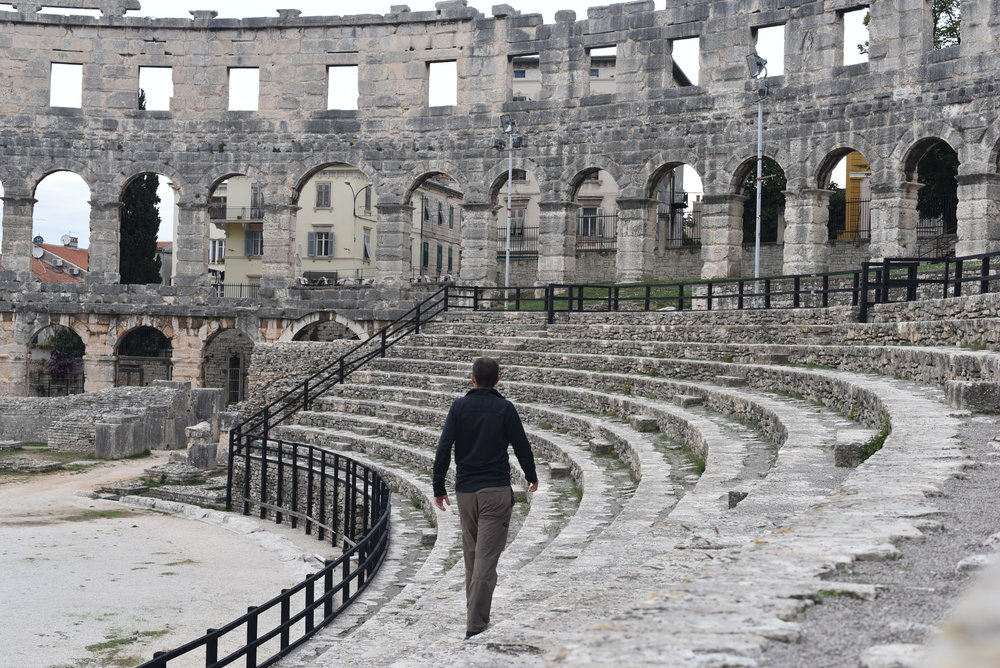 Walking along the seating area in the Pula Arena.