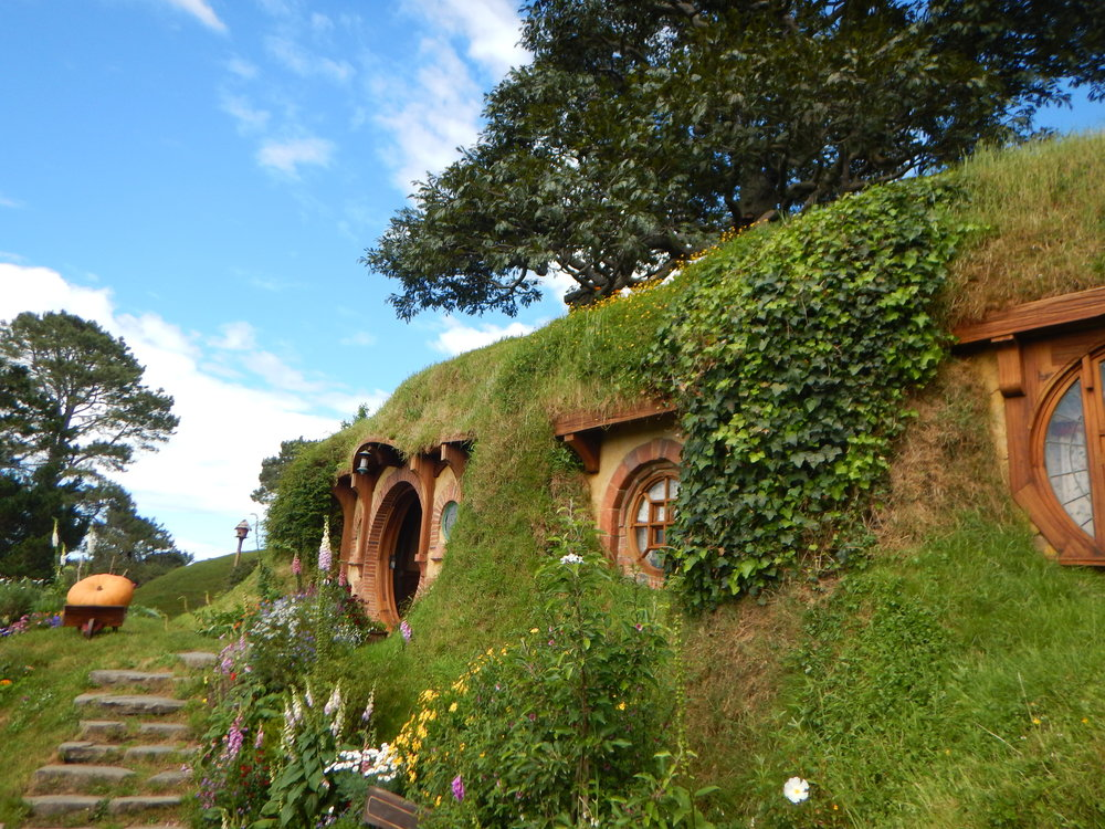 "The famous hobbit hole of bilbo baggins. the large tree at the top of the picture is fake! peter jackson requested this perfectly shaped tree be ""built"" for the movie. it looks so real! All 200,000 leaves were wired on one by one…"