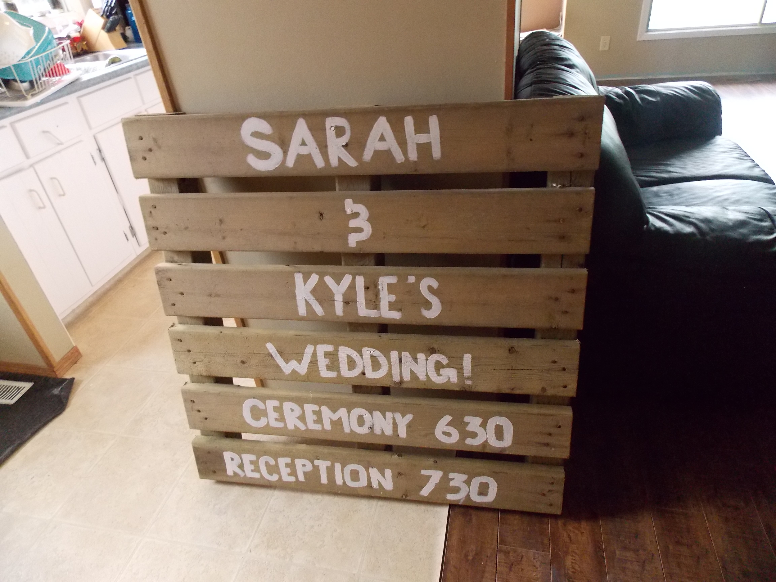 We made 2 signs like this because our venue is off a few gravel roads. One will be at the highway where guests will need to turn  off, and this one will be at the intersection of the venue! Just used some old pallets and white wall paint that I had laying around, and boom! A super cute, $0 decoration piece.