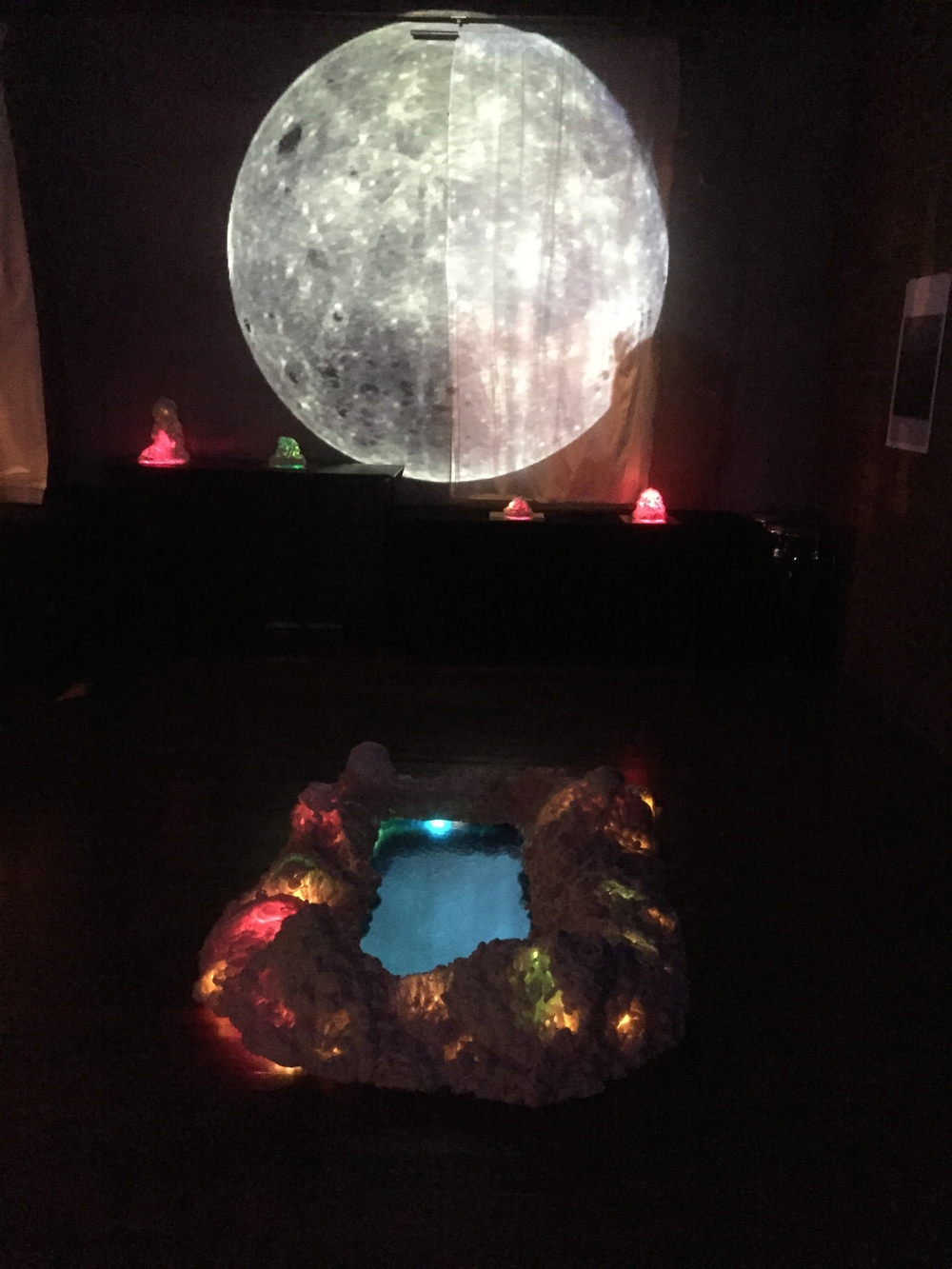 Floor sculpture and projected rotating moon on wall.