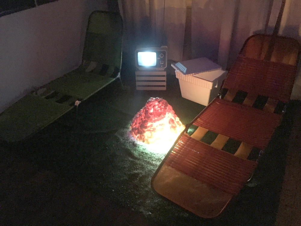 Astroturf, lawn chairs, TV, ice chest and rotating lava sculpture.