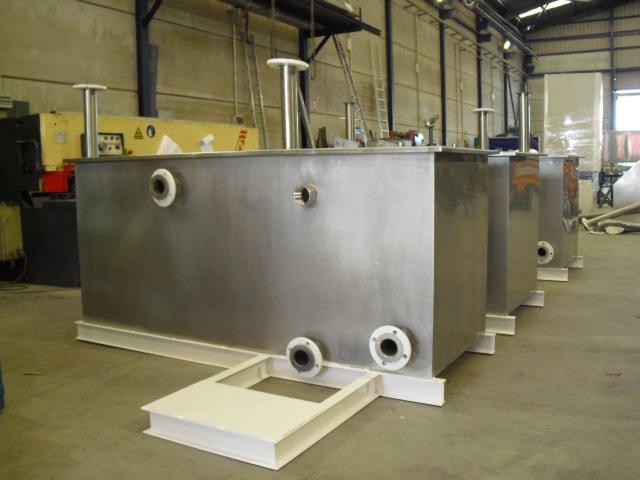Depósitos de acero inoxidable con accesorios como tuberías y conexiones sobre bancada de acero ordinario pintad, para procesos de cataforesis.