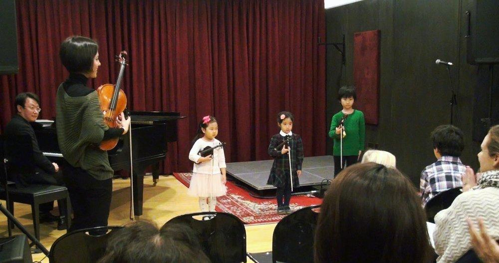 発表会の舞台のバイオリン塾の3人