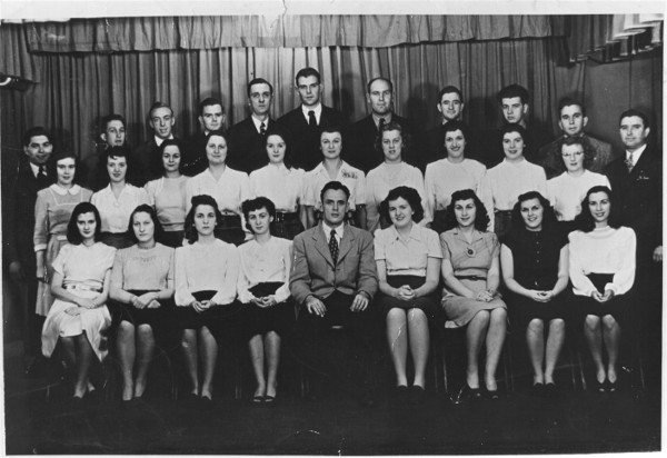 Back Row L to R: John Allgaier, Robert Charkowski, Clint Liggett, Vincent Redmond, Wayne Burdick, Peter VanderKley, Art Popp, Charles Shane, Windy Wunderlin, Tom Cizmadji, Emil Dornak. Middle Row L to R: Rose Marie Damm, Joan Ward, Jean Buist, Marie Thomas, Mary Alice Redmond, Mary Haiduk, Ruth Miller, Agnes Allgaier, Marilyn Wheeler, Mary Agnes Themins. Front Row L to R: Marge Schlick, Eva Bond, Dorothy Cizmadji, Frances Miller, Joe Salamun (Director), Rita Redmond, Dorothy Stender, Beatrice Themins, Edith Barinka.  Photographer: Bert Wylan of Kalamazoo.