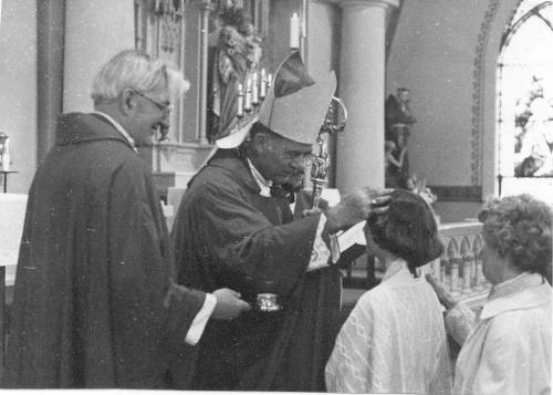 Fr. Fitzgerald, Bishop Donovan, and young person being confirmed with her sponsor in 1977