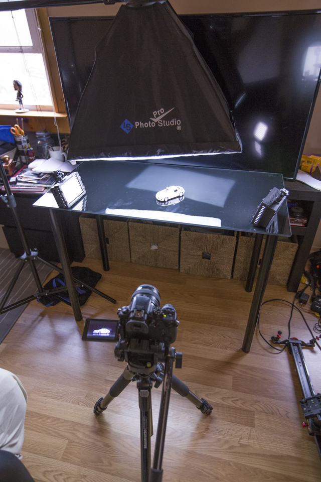 This is the setup on my glass computer desk with a softbox above, 2 LEDs, and my TV as the backdrop.
