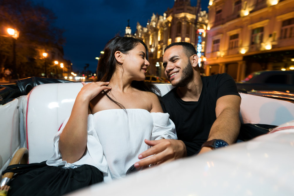 Since the rain stopped, we were able to get a nice convertible cab back to our place.  Cheers to these two love birds.  Sony A7RII, Zeiss Batis 18mm f/2.8 (iso1000, f/2.8, 1/160s)