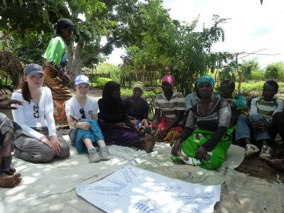 Fódhla Ní Dhálaigh (left) and Jessica Sweeney (right) sitting with members of a horticultural group supported by Gorta-Self Help Africa, Chitato village, Balaka, Malawi.