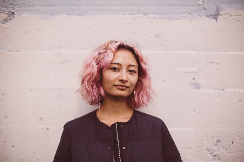 [A Hawai'ian and Chinese American Girl with pink hair and a dark blue jacket looking at the camera with a white wall background]