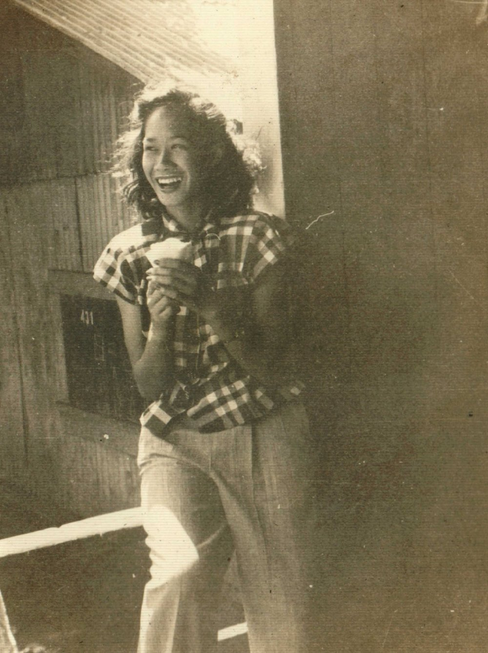 Lili'u's grandmother[ A black an white photograph of a Chinese and Hawai'ian women smiling and looking off to the side. She is holding a snowcone and wearing a plaid shirt with white pants]