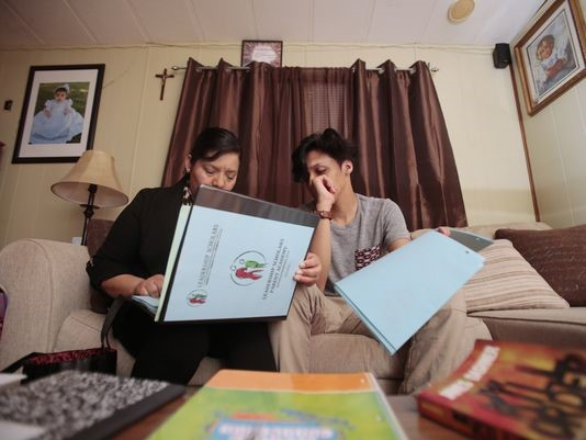 Maria Zuniga, left, and her son Jonathan Lopez, 14, right, look through her Leadership Scholars program binder, Tuesday, April 26, 2016, at her home in Sharonville, Ohio. The program is designed to help the mother of two to navigate the complex field of how to get her children to college. She has two middle-school children who now read, have access to books in the home, and are planning to attending college.(Photo: The Enquirer/Kareem Elgazzar)Buy Photo