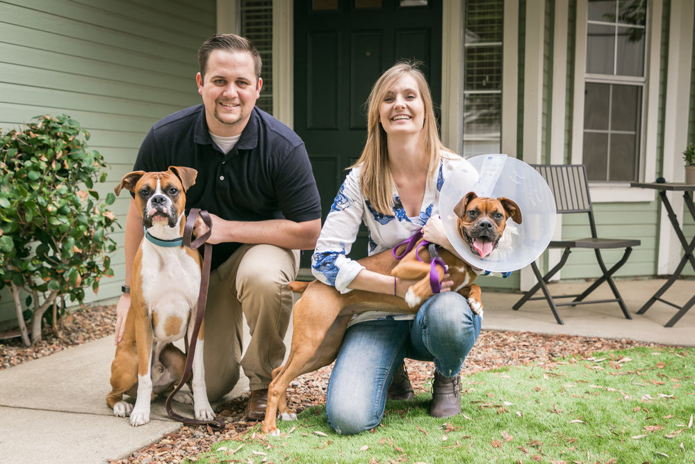 Tyler and Kelsie Plant posing with their two Boxers in front of their existing home on Rice Street in Roseville, California.