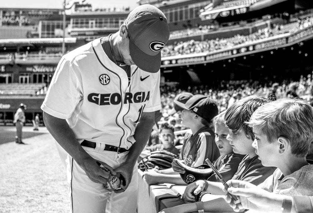 Members of the Georgia baseball team sign autographs during the Bulldogs' game against Missouri at SunTrust Park in Atlanta, Ga. on Saturday, April 8, 2017. (Photo by John Paul Van Wert)