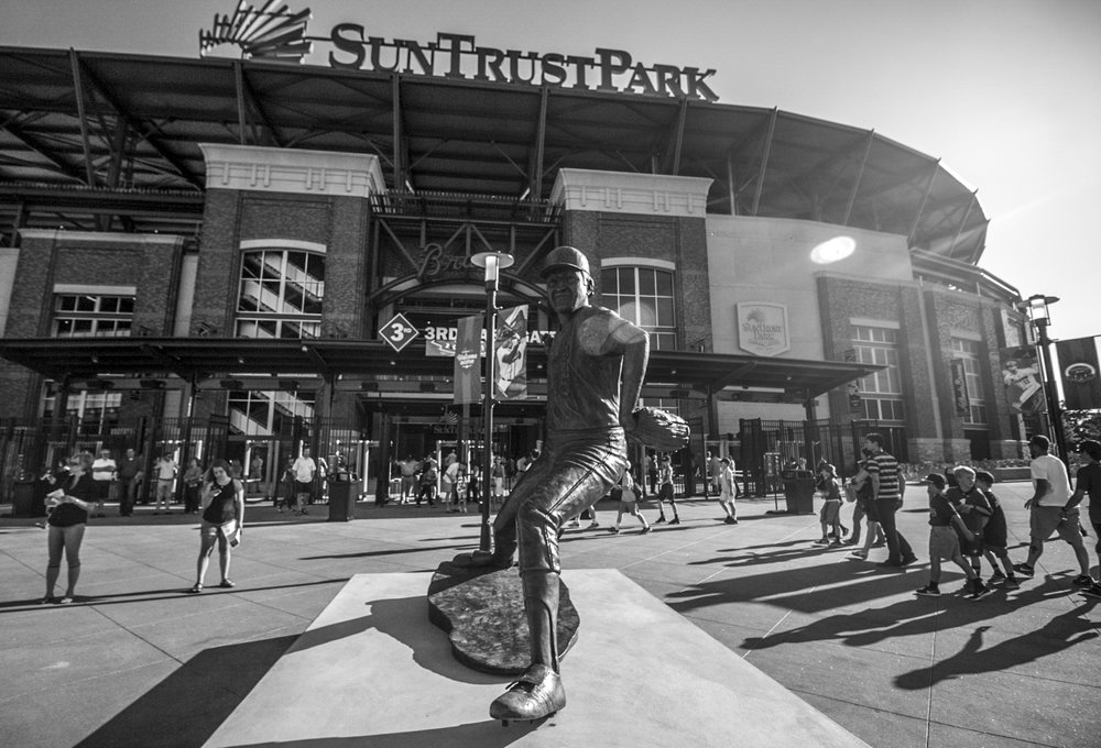 Baseball fans enter the 3rd base gate behind the statue of former Atlanta Braves pitcher Phil Niekro during the Bulldogs' game against Georgia Tech at SunTrust Park in Atlanta, Ga. on Tuesday, May 9, 2017. (Photo by John Paul Van Wert)