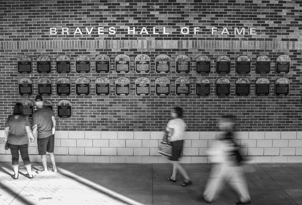 Baseball fans pass by the Atlanta Braves hall of fame wall during the Bulldogs' game against Georgia Tech at SunTrust Park in Atlanta, Ga. on Tuesday, May 9, 2017. (Photo by John Paul Van Wert)
