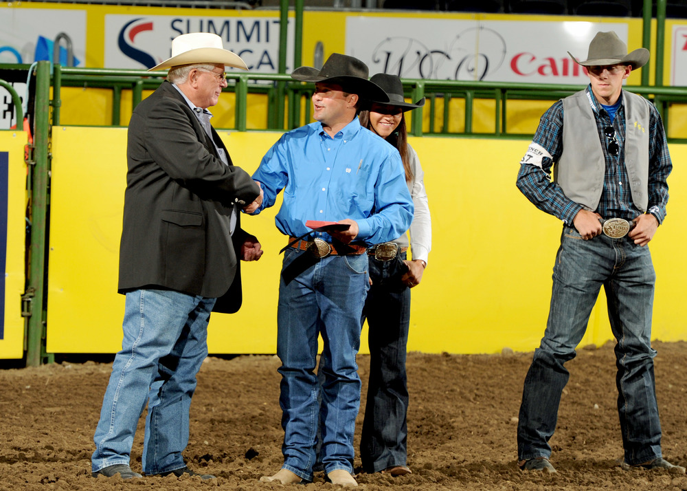 Former NIRA commissioner John Smith presents Jesse Segura from Feather River College the 2015 Coach of the Year award while his student athletes look on. CNFR photo by Dan Hubbell.
