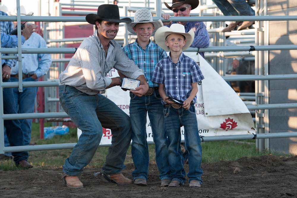 Josh Birks is awarded his Jensen Silver trophy buckle from Beau and Jesse Gardner at the 9th Annual Buffalo Hills Bull Riding in Arrowwood, AB on June 25th. Photo by Jack Vanstone/Legendary Photoworks.