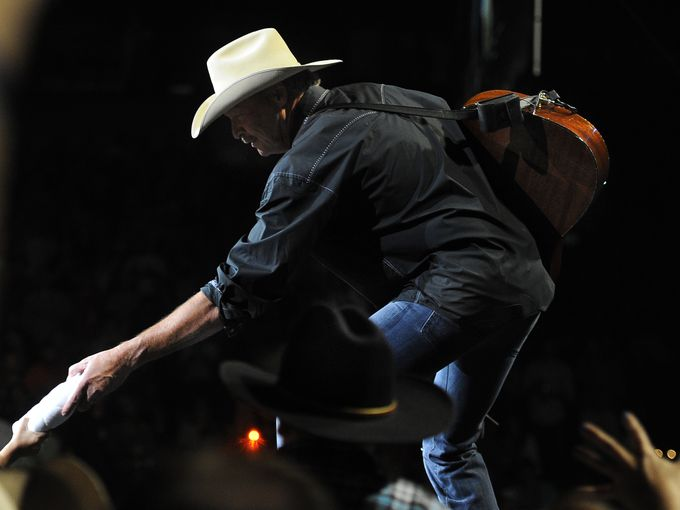 Alan Jackson reaches down to hand a fan a T-shirt.  George Walker IV / The Tennessean