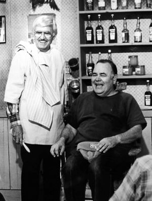 "Jonathan Winters sits in Archie Campbell's barber chair during an episode of ""Hee Haw."""