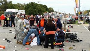 Bystanders help the injured after a vehicle crashed into a crowd of spectators during the Oklahoma State University homecoming parade, causing multiple injuries, on Saturday, Oct. 24, 2015 in Stillwater, Oka. (David Bitton/The News Press via AP)