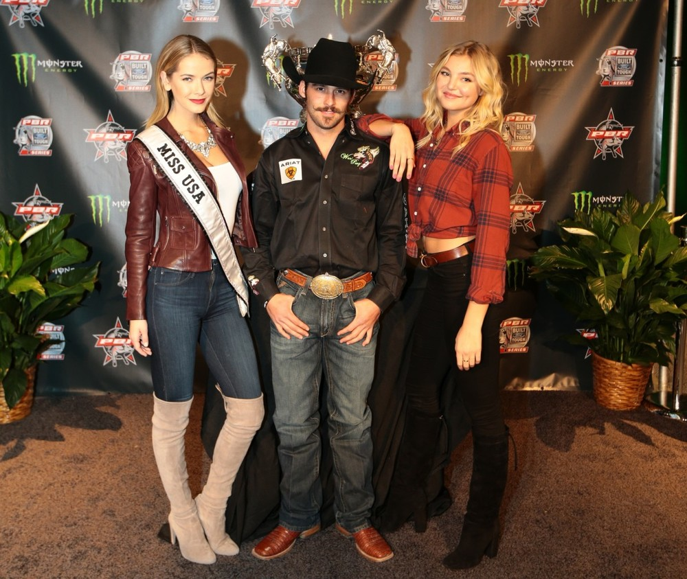 Miss USA Olivia Jordan and Victoria Secret model Rachel Hilbert pose with a PBR cowboy before the Monster Energy Buck Off at the Garden. (Photo by Andy Watson)