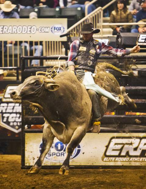 Cody Campbell of Summerville hangs on tight to a bull named Wolf on Wall Street while competing during the Elite Rodeo Athletes Premier Tour stop Saturday night at the Bank of the Cascades Center at the Deschutes County Fair & Expo Center in Redmond. Photo by Andy Tullis/The Bulletin