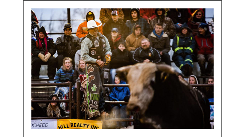 The cold but supportive crowd looks on as Birks eyes up the bull he just rode. The community of Lamont was amazing in the unpredictable Alberta weather. They came prepared and stayed to the very end! Photo courtesy of Legendary Photoworks