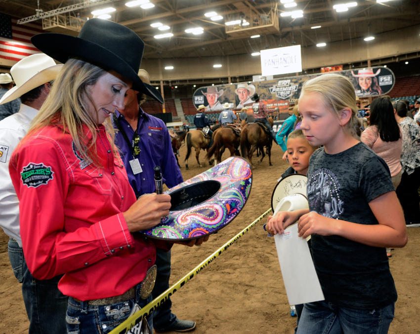 Charmayne James autographs a hat for Taylor Rolan, 10 of Belen. (Jim Thompson/Journal)