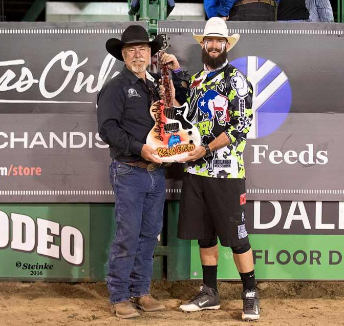 Reno Rodeo President, Scott Peterson presents Weston Rutkowski with the Championship Guitar.