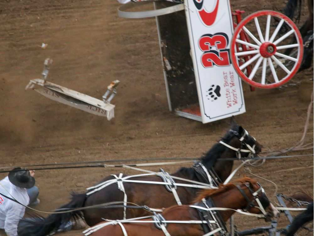 Chuckwagon driver Rick Fraser flies from his seat as his wagon flips over at the start of Heat 4 of the Rangeland Derby chuckwagon races at the Calgary Stampede on Sunday July 10, 2016. It was announced after the incident that neither Rick Fraser nor any of the horses were hurt. MIKE DREW /  CALGARY HERALD