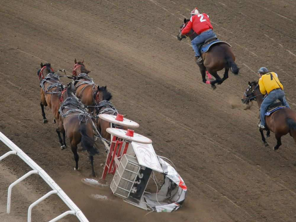 Outriders try to catch up to their assigned wagons as the pass the chuckwagon of Rick Fraser that flipped over at the start of Heat 4 of the Rangeland Derby chuckwagon races at the Calgary Stampede on Sunday July 10, 2016. It was announced after the incident that neither Rick Fraser nor any of the horses were hurt. MIKE DREW / CALGARY HERALD