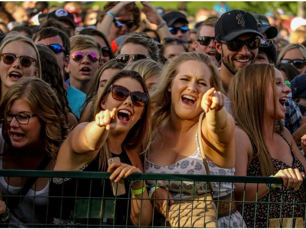 Singing along with Chris Young at Country Thunder. Fans faced long lineups for food and suds but were in good spirits, nonetheless. MIKE DREW /  POSTMEDIA