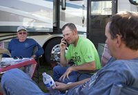 Tim Bridwell (center) takes a phone call while enjoying a little downtime with Brent Gibson (left) and Eric Layton (right) at the St. Paul Rodeo in St. Paul, Oregon in July. Bridwell, a partner of Growney Brothers Rodeo Company, travels along the West Coast providing live stock for rodeos. (COURTESY PHOTO)