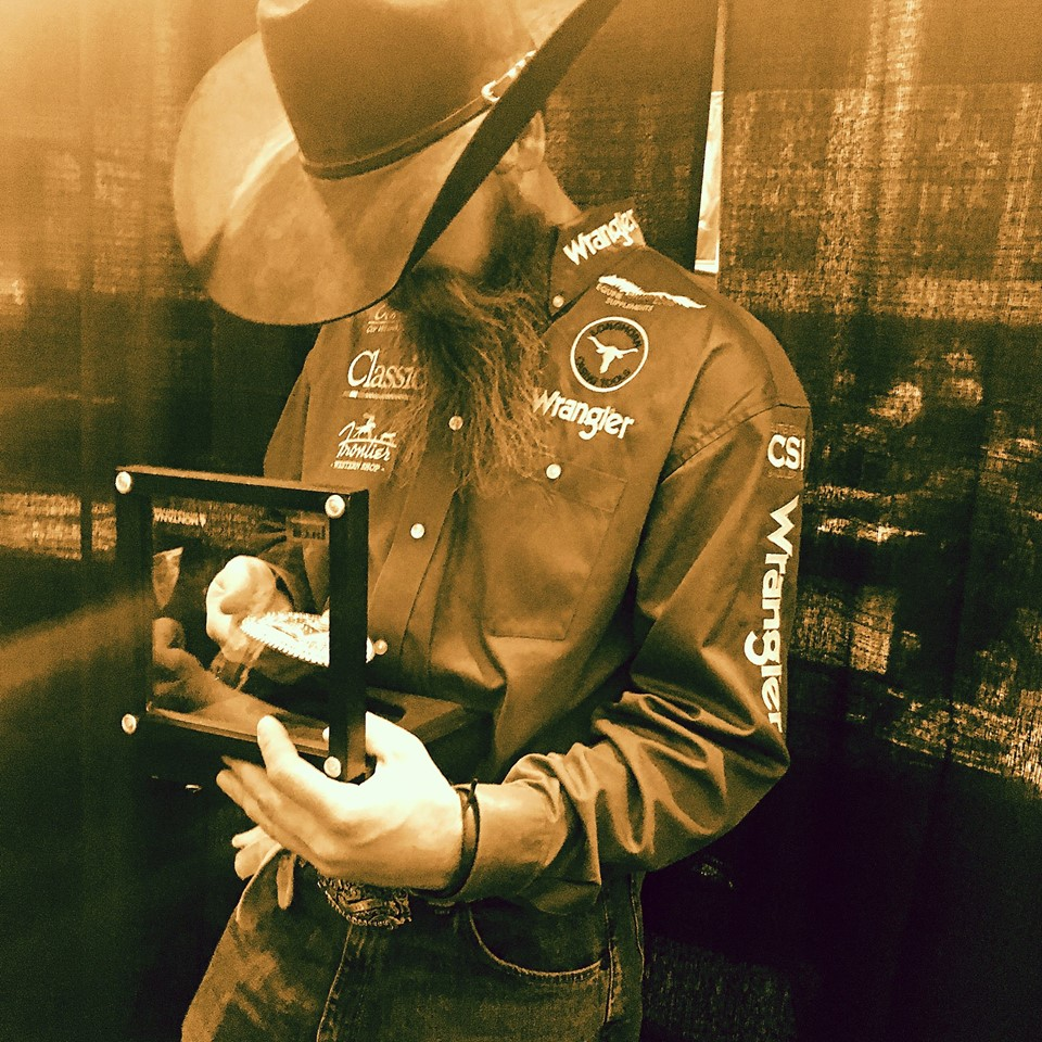 2016 team roping (heeler) world champion Jeremy Buhler checks out his new gold buckle in the #WranglerNFRpress room.#fearthebeard. PRCA Photo by Bryan Oller.