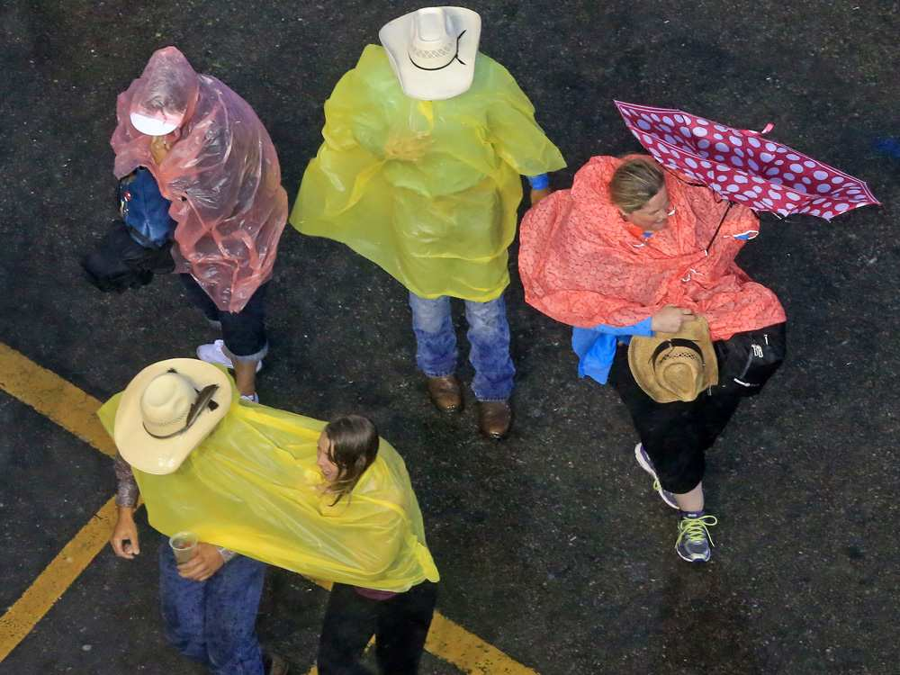 Stampede visitors race for the cover of the grandstand when an intense thunderstorm swept through Calgary during the GMC Rangeland Derby on Monday evening July 10, 2017. GAVIN YOUNG /  CALGARY HERALD