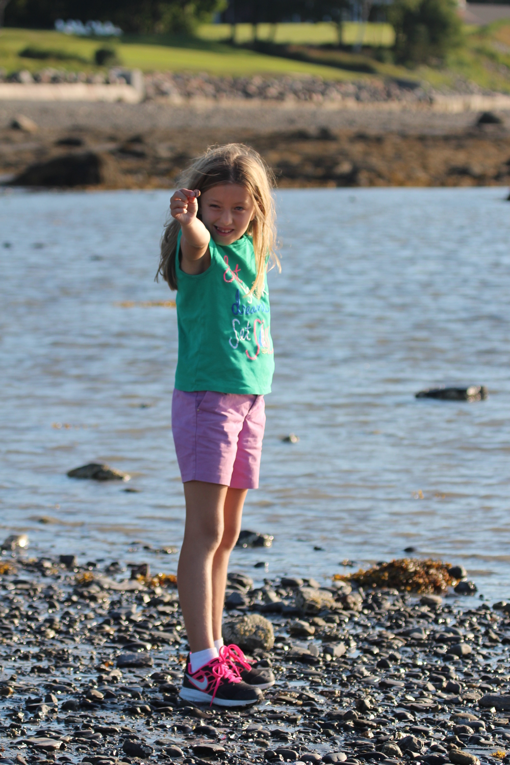 Showing off the great skipping rock she found to put her new found knowledge to the test.