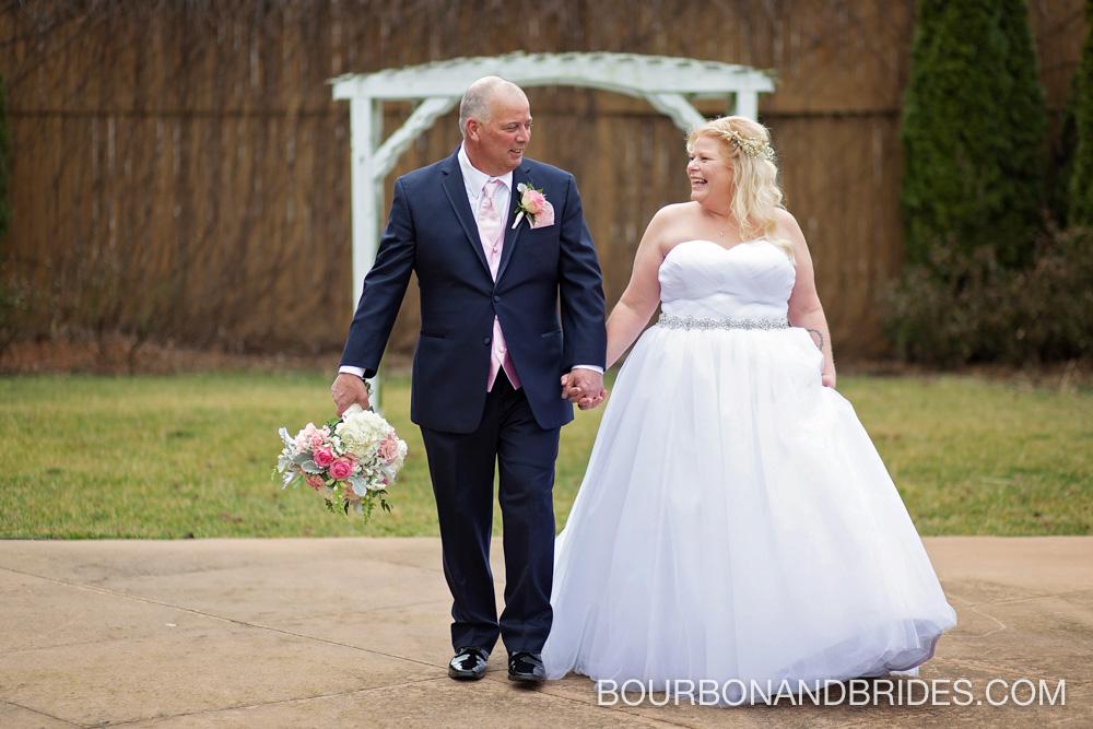 bride-groom-walking-barrel-house-wedding.jpg