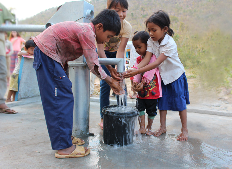 Cambodian children enjoying their new water well