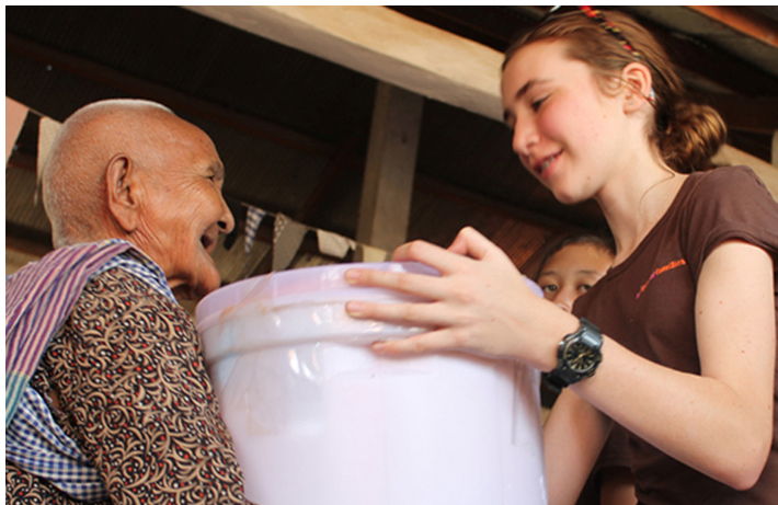 Maddie giving a new water filter to a Cambodian villager