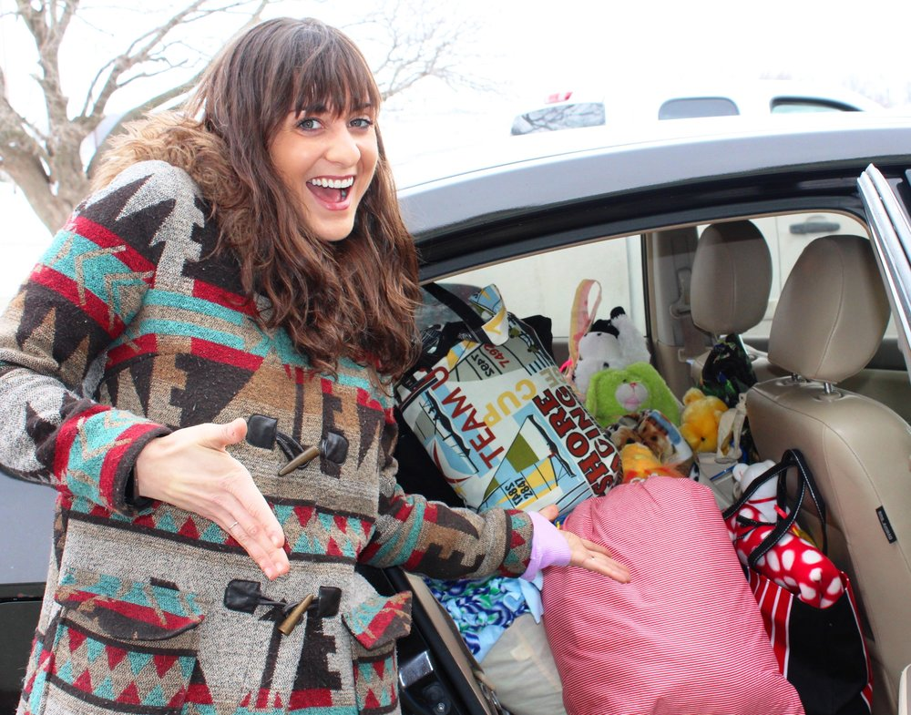 Angela Moon Lins-Eich, a Care Bags Foundation distributor, filling her car with care bags destined for children.