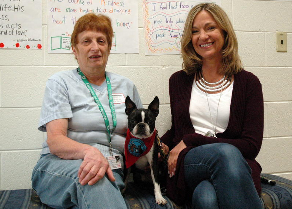 Kona with her owner and trainer Sandy Cornell, left, and Reed Intermediate School fifth grade teacher Karen King.