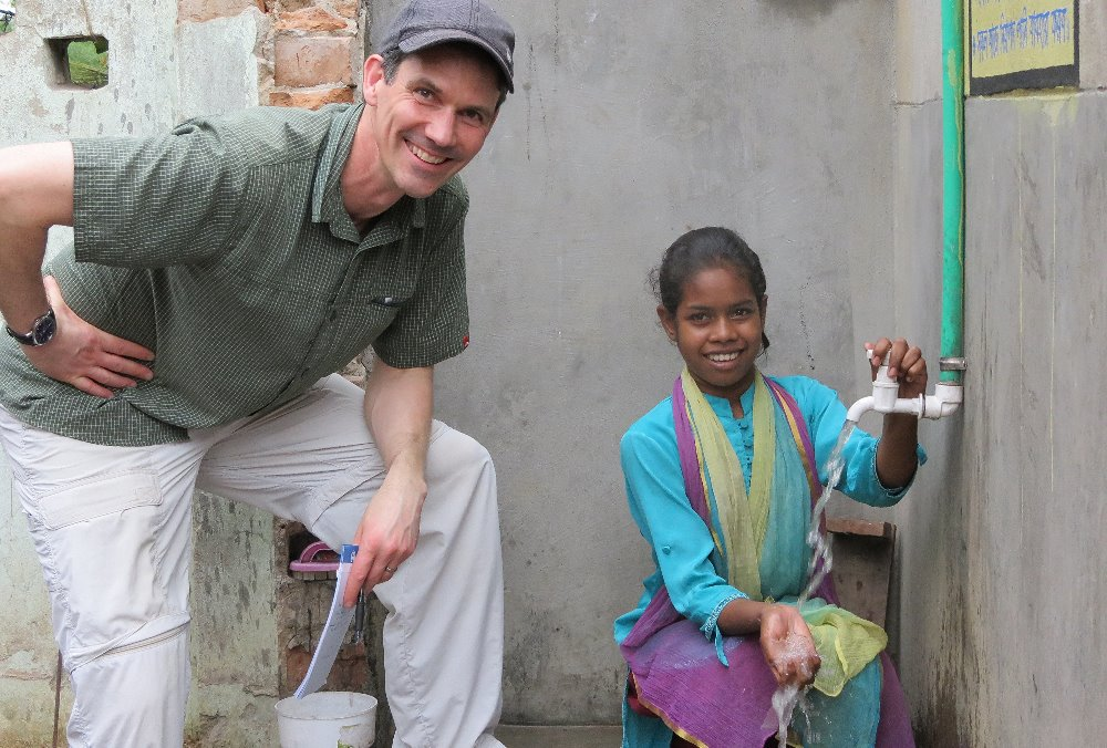 Kirk Anderson, Director of International Programs, with Isra at her new water tap