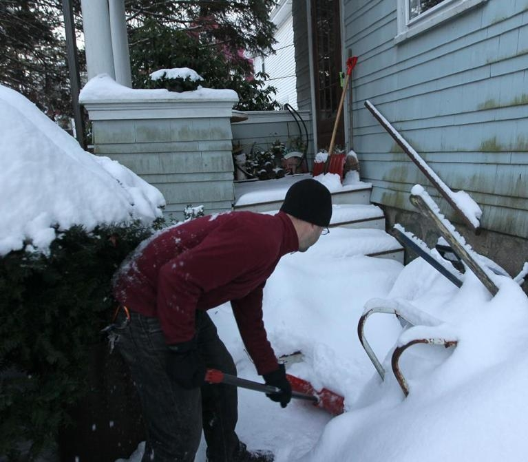 A volunteer shovels snow for an elderly neighbor