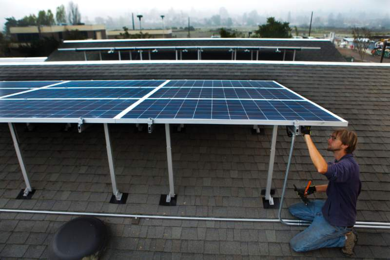 Adjustments are made on the newly installed COTS solar panels (photo credit: Crissy Pascual of the Argus Courier)