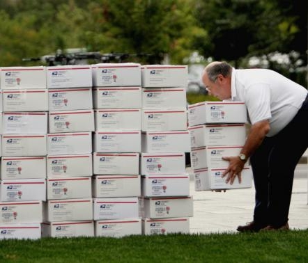 A volunteer piles up care packages bound for troops overseas.  (photo credit: Wendy Maeda/Boston Globe Staff)