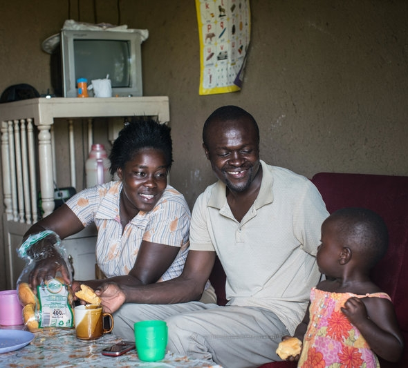 Otieno, his wife, and daughter, Gloria, eat lunch  (photo credit: Nichole Sobecki for NPR)