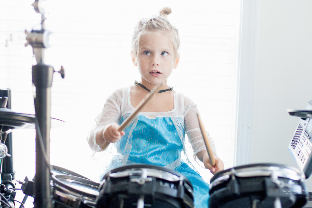 little girl playing drums in a princess dress