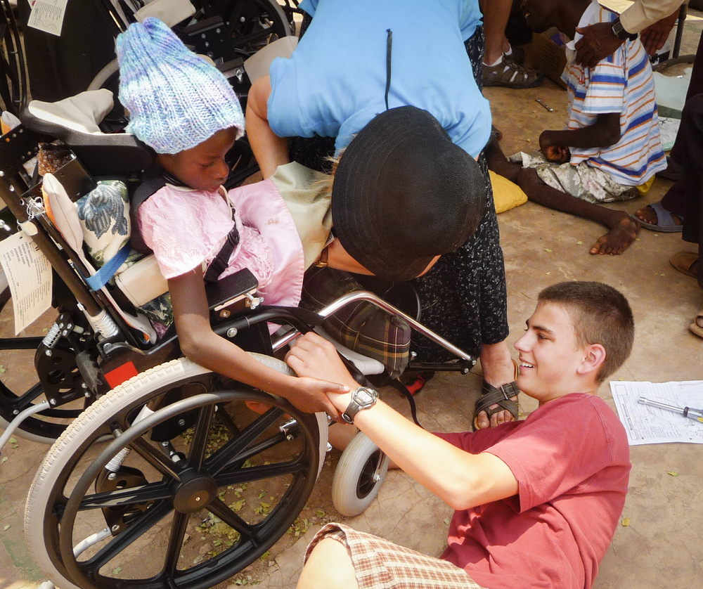 non-profit volunteer youth helps child in wheelchair and comforts the child as the wheelchair is being properly fitted to suit the child's specific needs