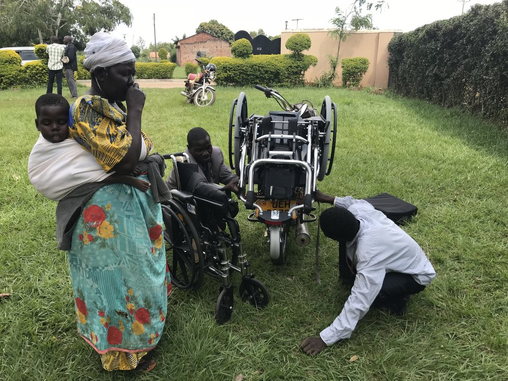 Most of our wheelchair recipients arrive by a motorcycle taxi. Here the driver is tying a ROCKIT chair onto his motorcycle. Somehow driver, Mama and child manage to fit on as well!